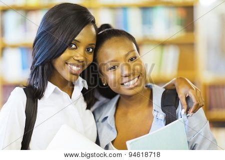 portrait of pretty african american college friends together in library