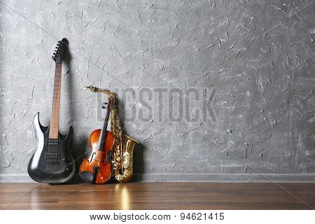 Electric guitar, saxophone and violin on gray wall background