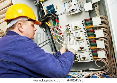 electrician builder at work with tester measuring high voltage and current of power electric line in electical distribution fuseboard. Focus on hands poster