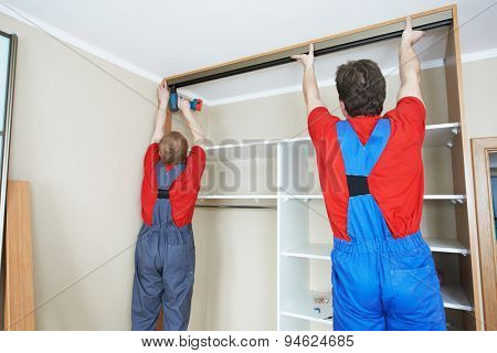 Two carpenters workers joint and settle home built-in cupboard poster
