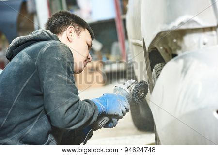 auto mechanic worker sanding polishing bumper car at automobile repair and renew service station shop by polishing grinding machine