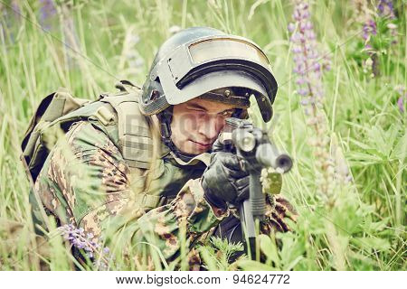 military. soldier in uniform targeting with assault rifle outdoors