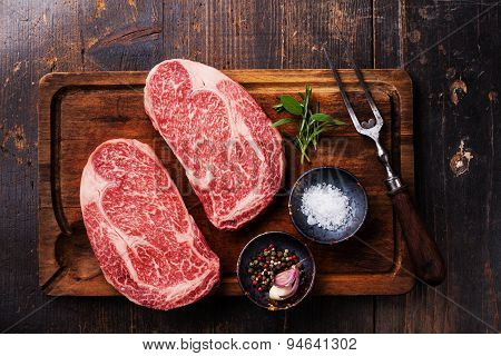 Two Raw Fresh Marbled Meat Black Angus Steak Ribeye, Seasonings And Meat Fork On Dark Wooden Backgro
