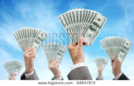 Venture capital or crowd funding finance and investment concept businessmen holding up dollar currency aloft
