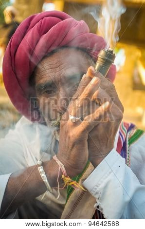 GODWAR REGION, INDIA - 14 FEBRUARY 2015: Elderly Rabari tribesman with red turban and blanket smokes chillum. Rabari or Rewari are an Indian community in the state of Gujarat.