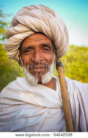GODWAR REGION, INDIA - 14 FEBRUARY 2015: Elderly Rabari tribesman with white turban and blanket around the shoulders and axe. Rabari or Rewari are an Indian community in the state of Gujarat.
