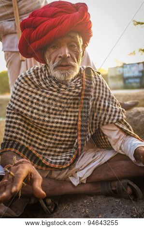 GODWAR REGION, INDIA - 14 FEBRUARY 2015: Elderly Rabari tribesman with red turban and blanket around the shoulders smokes beedi. Rabari or Rewari are an Indian community in the state of Gujarat.