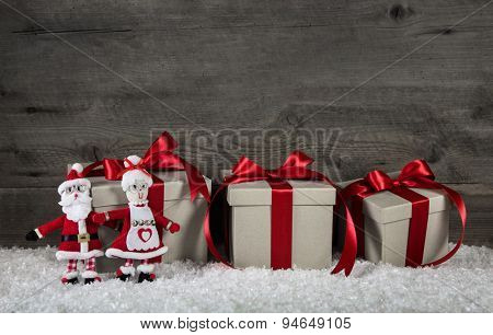 Red christmas presents on wooden grey background with mr. and mrs. santa.