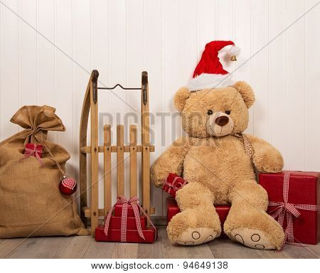 Teddy bear as a santa with an old wooden sleigh and red christmas presents.