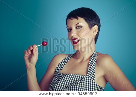 Sugarplum, happy young woman with lollypop  in her mouth on blue background
