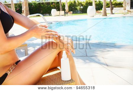 Woman applying sun cream. Sexy blond woman in bikini relaxing beside a swimming pool. Sunscreen protection summer body. Close up poster