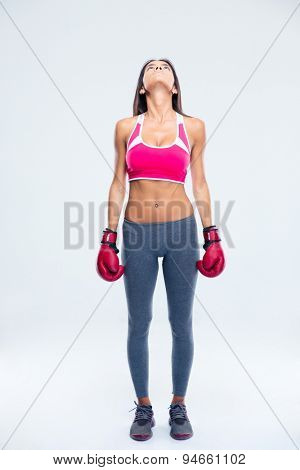 Full length portrait of a fitness woman in boxing gloves looking jup over gray background