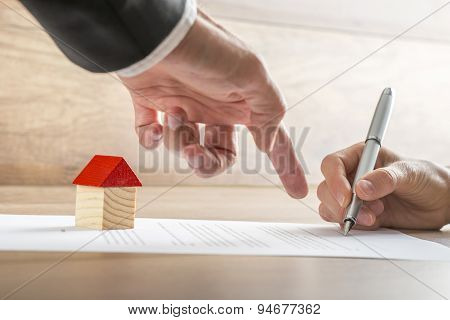Real Estate Agent Showing His Client Where To Sign A Contract Of House Sale