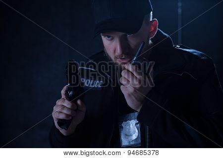 Policeman Holding Radio And Gun