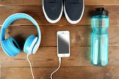Sport shoes with bottle of water and headphones on wooden background poster
