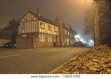 High Street Tarvin Cheshire UK - October 31 2016: Old arts and crafts house in a small village at misty Halloween night.