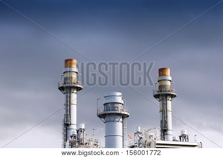 The smoke stack of power plant factory with the gray cloud