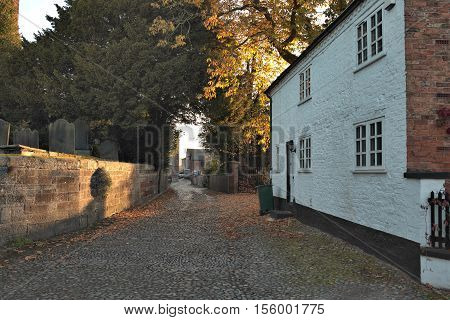 Tarvin Cheshire UK. Dawn light through road towards old farm buildings.