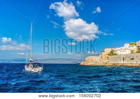 Hydra island on a summer day in Greece. Beautiful landscape with sea and island, and a boat sailing.