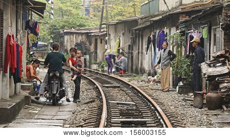 Hanoi, Vietnam - Mar 15, 2015: Usual life, transportation and houses on the railway track. It's dangerous to live here but poor people don't have many choices.