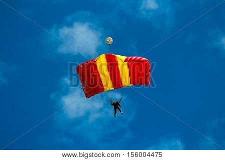 Skydiver and colorful parachute on blue sky background