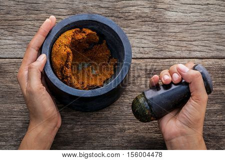 The Women Hold Pestle With Mortar And Spice Paste . The Red Paste Ingredients For Red Curry On Rusti