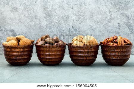 Whole Almonds,whole Walnuts ,whole Hazelnut And Pecan Nuts In Wooden Bowl Setup With Stone Backgroun