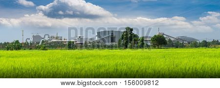 View of a factory in the middle of a green rice field. Factory pipes polluting air on a silent.