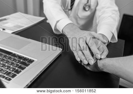 doctor's hands holding patient's hand for encouragement and empathy black and white. Doctor man. Doctor woman. Doctor hand. Doctor shake.