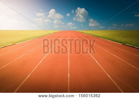 Red Running track on blue sky. Athlete track or running track with sky sunset background