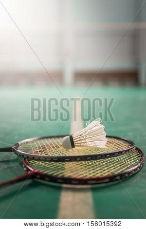Badminton ball (shuttlecock) and racket on court floor. Badminton sports. Play badminton. Badminton exer cise. Badminton tournament. Badminton training. Badminton feather. Badminton health. Shuttle badminton.