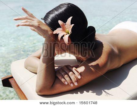 Beautiful  woman laying near the ocean and taking sunbath