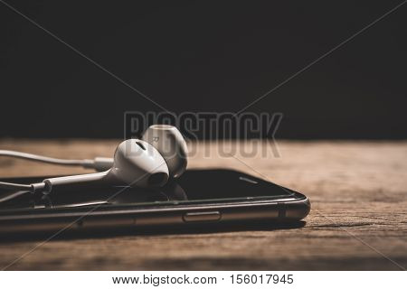 Headphone and phone media portable on dark tone. headphone and smartphone on wood table. headphones and phone depth of field. White headphone and black smartphone. selective focus of headphone.