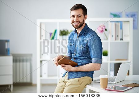 Attractive designer sitting on table in studio holding appointment book