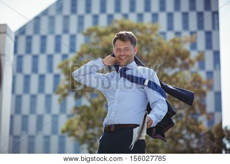 Portrait of businessman holding blazer and newspaper near office building