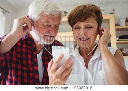 Senior couple listening to music on smartphone in kitchen