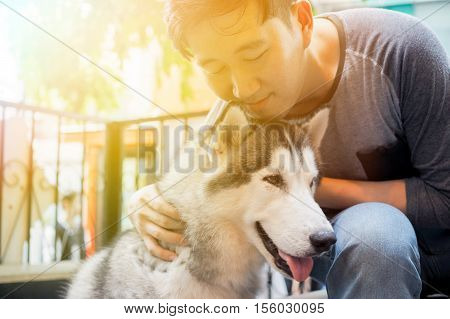 Young Asian male dog owner hugging and embracing the Husky Siberian dog pet with love and care.