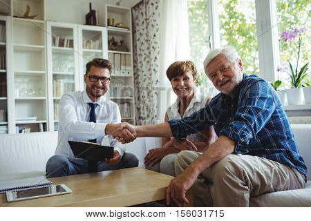 Portrait of financial advisor shaking hands with senior man in living room