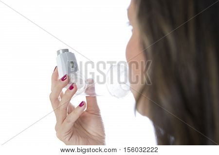 Young woman is inhaling the medicament from the pressurized cartridge inhaler placed on an inhalation chamber - Rear view - Isolated on a white background