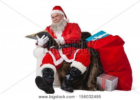 Santa reading bible with sack of christmas present beside him against white background