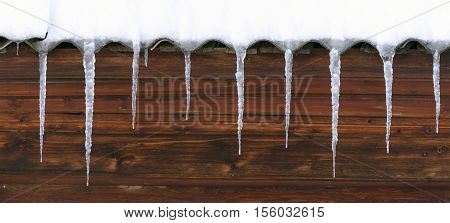 Icicles Hang From The Undulating Roof. The Wall Of The Wooden House. Hdr - High Dynamic Range.