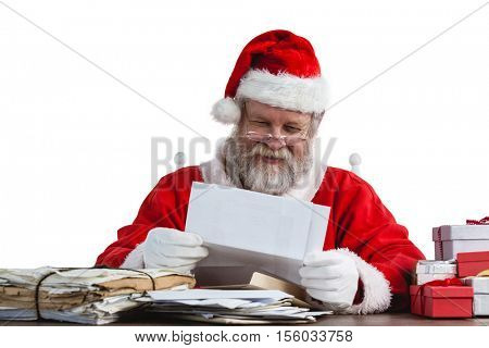 Santa claus sitting on chair and reading a letter