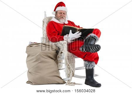 Santa claus reading bible with sack of christmas present beside him against white background