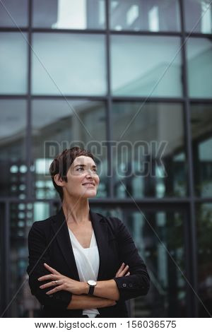 Smiling businesswoman standing with arms crossed in office premises
