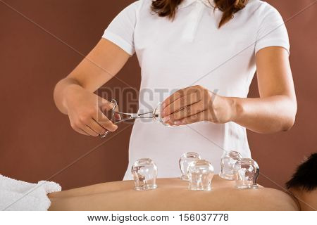 Close-up Of A Therapist Giving Cupping Therapy To Man In Spa