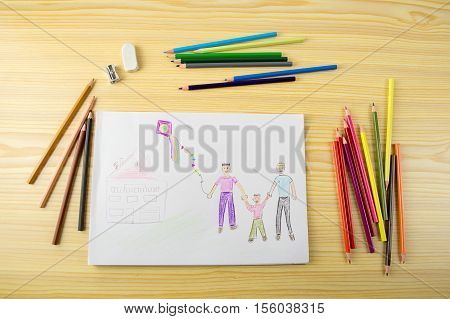 Shot of a drawing with painting supplies and pencils on a wooden table with a picture of a gay couple with their daughter