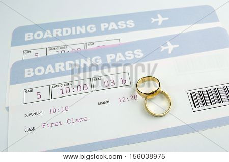 close up of a wedding rings on an airline boarding passes of a honeymoon