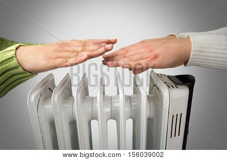 couple warm up hands over electric heater
