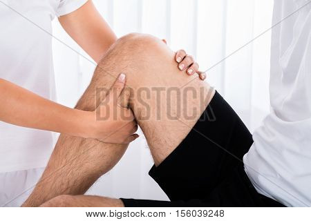 Close-up Of A Therapist Hand Massaging Man's Leg In Spa