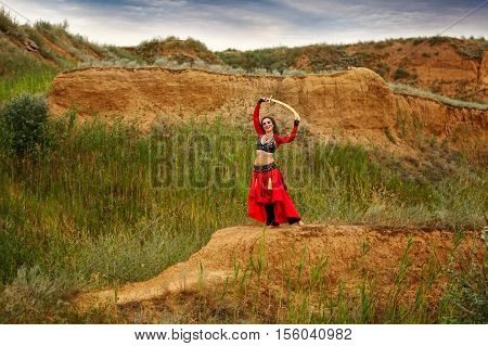 Passionate dance with a sword. Tribal style. Attractive girl in costume dancing outdoors. Sand dunes. Nomads.